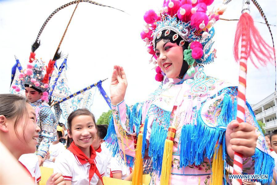 A young Wu Opera actress interacts with students during an event in celebration of the International Children\'s Day in Jiande City, east China\'s Zhejiang Province, May 30, 2019. (Xinhua/Ning Wenwu)