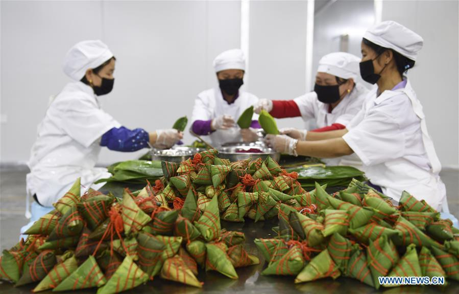 Workers make colorful Zongzi, pyramid-shaped dumplings made of glutinous rice wrapped in bamboo or reed leaves, at a factory in Taijiang County, southwest China\'s Guizhou Province, June 2, 2019. Different plant juices are used to color the glutinous rice when making the colorful Zongzi. Zongzi is a traditional food for the Dragon Boat Festival, which falls on June 7 this year. (Xinhua/Liu Kaifu)