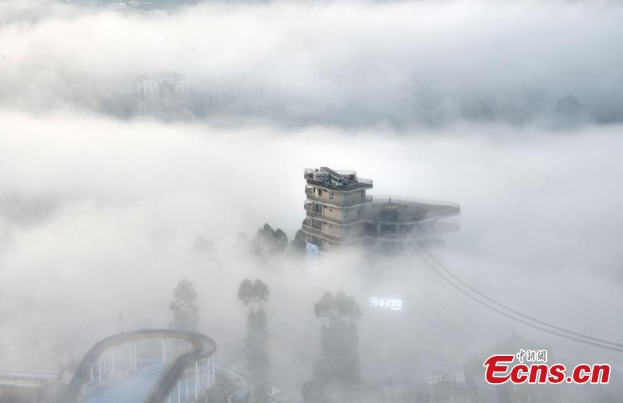 Fog shrouds buildings in the Wine Town, near the Yangtze River, in Fuling District, Chongqing Municipality, June 2, 2019. (Photo: China News Service/Shi Wei)
