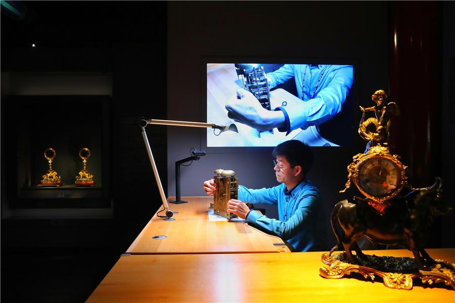 <?php echo strip_tags(addslashes(Wang Jin, an antique clock restorer, demonstrates his craftsmanship to visitors at the exhibition. (Photo provided to China Daily)