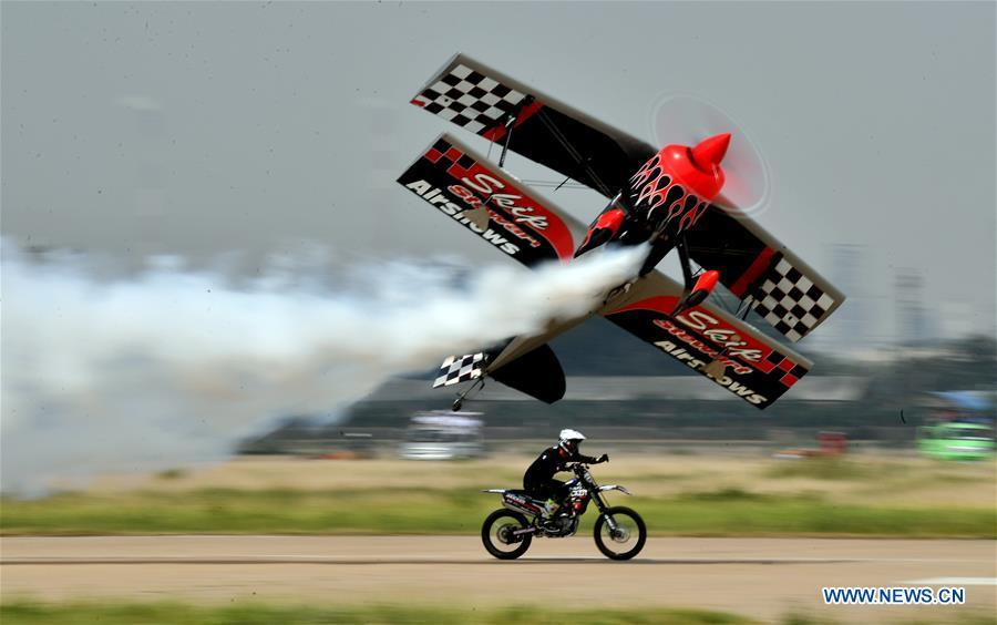 An enthusiast flying a small plane races with a motorcycle during the opening of the 11th Air Sports Culture and Tourism Festival in Anyang, central China\'s Henan Province, June 3, 2019. The event kicked off Monday in the city of Anyang, attracting air sports fans from home and abroad. (Xinhua/Li Jianan)