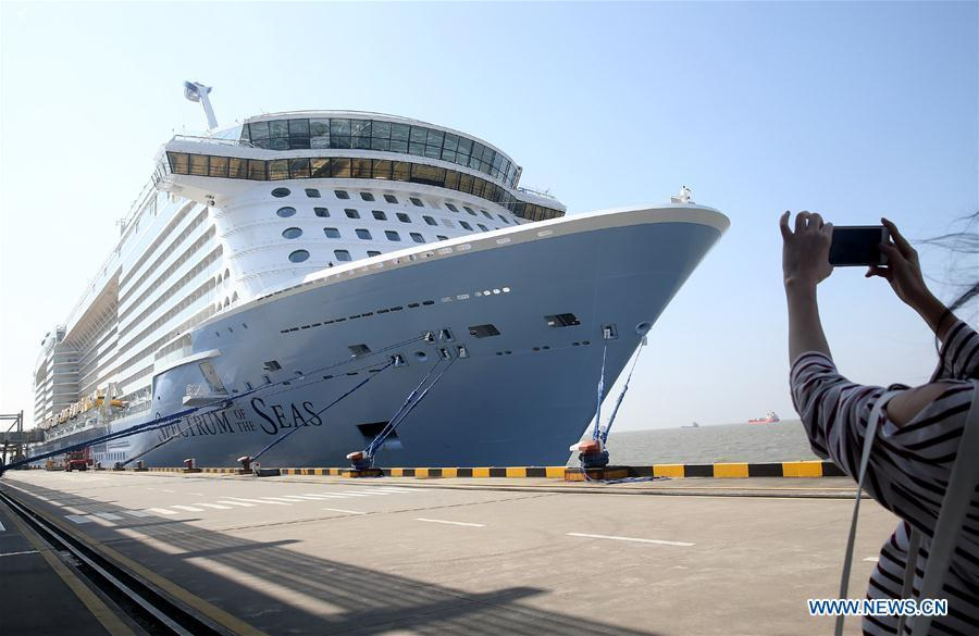 A tourist takes photos of the Royal Caribbean International cruise ship \