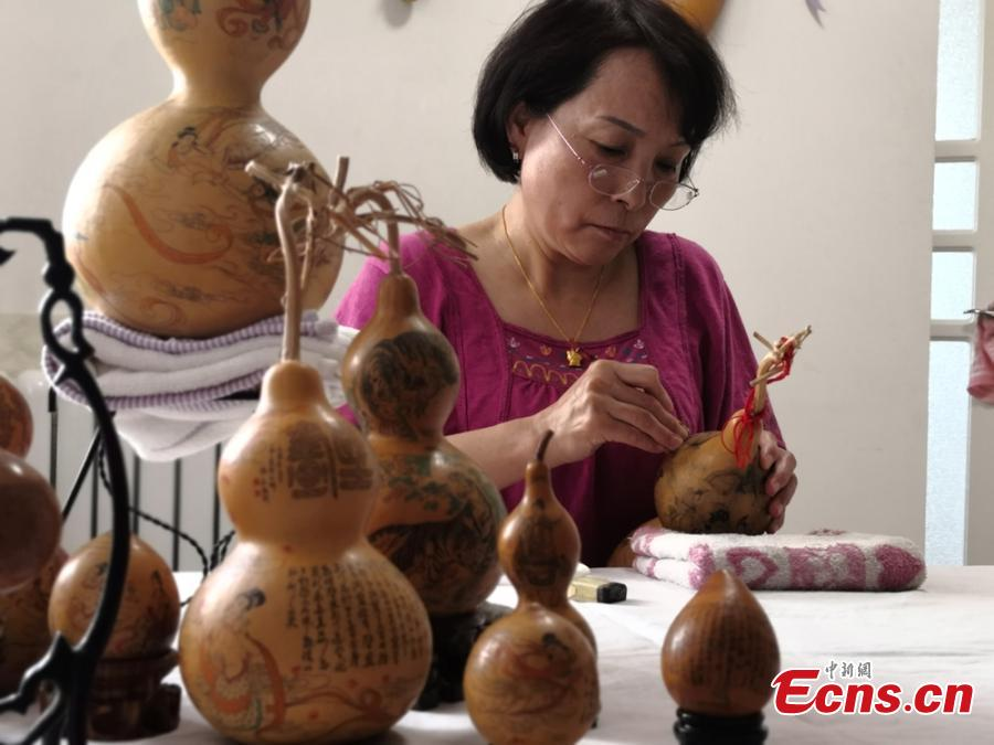 Craftswoman Chen Bing puts the final touch to a gourd in Lanzhou City, Gansu Province in June 2019.  The second generation in her family to make artistic creations on gourds, she carved  characters sometimes just one millimeter in size. (Photo: China News Service/Yang Na)