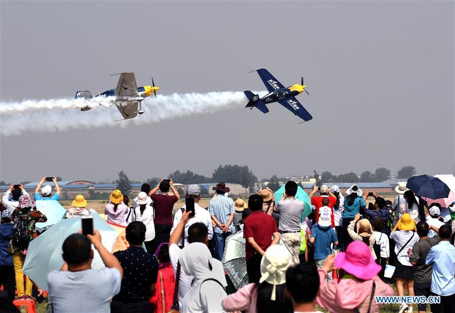 People watch an aerobatic show by enthusiasts in air sports during the opening of the 11th Air Sports Culture and Tourism Festival in Anyang, central China\'s Henan Province, June 3, 2019. The event kicked off Monday in the city of Anyang, attracting air sports fans from home and abroad. (Xinhua/Li An)