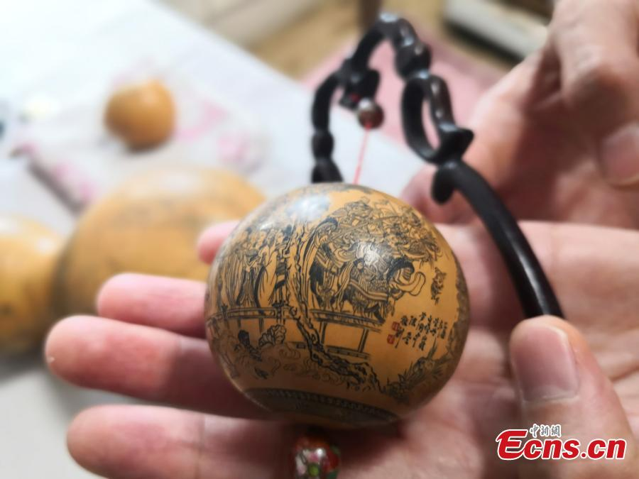 Craftswoman Chen Bing shows a gourd she carved in Lanzhou City, Gansu Province in June 2019.  The second generation in her family to make artistic creations on gourds, she carved  characters sometimes just one millimeter in size. (Photo: China News Service/Yang Na)