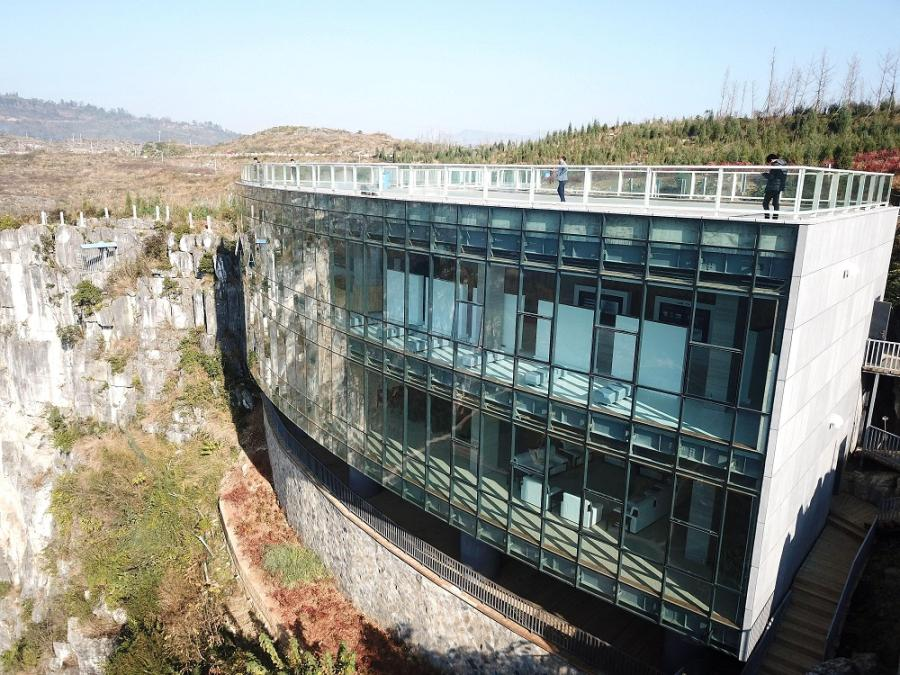 The Limestone Galleay has been built at the edge of a 165-meter-high cliff in Anlong county, Southwest China\'s Guizhou Province. (Photo by Liu Chaofu/for chinadaily.com.cn)  An art museum has been built at the edge of a 165-meter-high cliff in Anlong county, Southwest China\'s Guizhou Province. It is the first art museum, named Limestone Galleay, built at the top of a cliff in China.  Constructed on top of the cliff, the museum covers an interior area of 800 square meters and includes two exhibition floors, a meeting room and an outdoor sightseeing platform on the roof.  The museum features an arcade-like frontage and its exterior is a glass curtain wall that allows visitors to enjoy the scenery of the hill and valleys from the top.