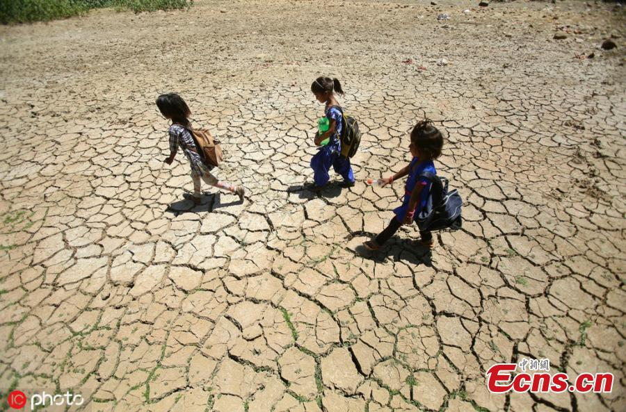 Indian school children walk on the dried pond after attends school on a hot summer day outskirts of Jammu, India, Thursday, May.30,2019.(Photo/IC)