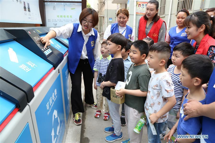 A volunteer illustrates the knowledge of garbage sorting to children in Hefei, east China\'s Anhui Province, June 4, 2019. Various activities are held across the country to raise people\'s awareness of garbage sorting and help them develop the habit of waste classification. (Xinhua/Fu Jun)