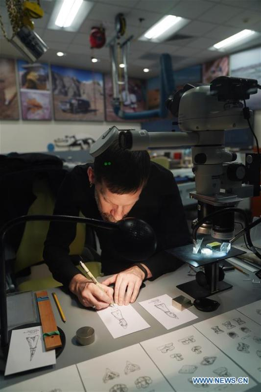 A staff member draws pictures of small fossils in the new dinosaur and fossil hall of the Smithsonian\'s National Museum of Natural History in Washington D.C., the United States, on June 4, 2019. The Smithsonian\'s National Museum of Natural History will reopen its dinosaur and fossil hall \