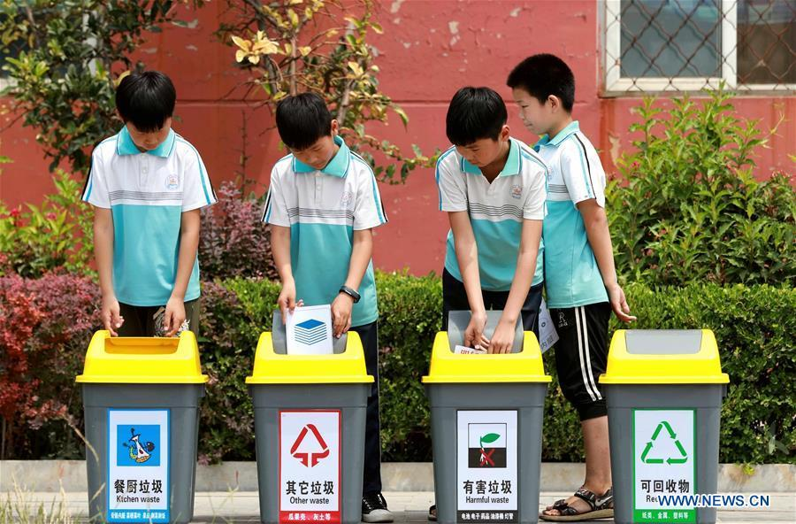 Students throw wastes into rubbish bins according to garbage sorting in Xingtai, north China\'s Hebei Province, June 4, 2019. Various activities were held across the country to raise people\'s awareness of garbage sorting and help them develop the habit of waste classification. (Xinhua/Song Jie)