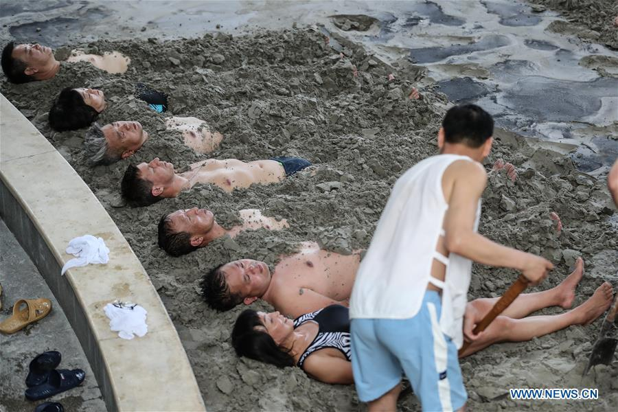 A Russian patient (4th L) receives physiotherapy through thermal mineral mud-bath at Tanggangzi Hospital in Anshan, northeast China\'s Liaoning Province, June 4, 2019. Featured with traditional Chinese medicine therapy, Tanggangzi Hospital has attracted many Russian patients who come here to receive rehabilitation treatments, such as acupuncture, physiotherapy, cephalic magnet therapy. The hospital received more than 6,000 Russian patients in one year at the peak. (Xinhua/Pan Yulong)