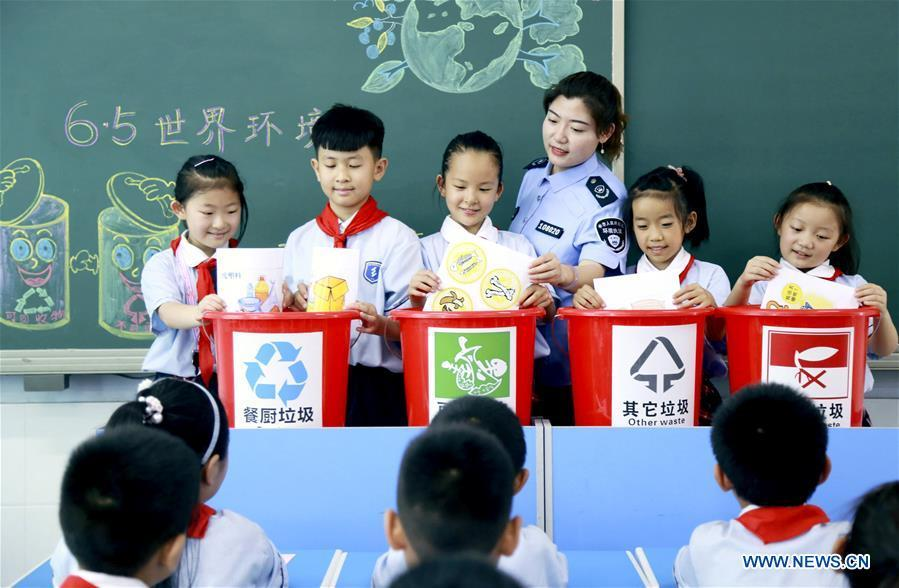 Pupils learn the knowledge of garbage sorting at an elementary school in Xingtai, north China\'s Hebei Province, June 4, 2019. Various activities are held across the country to raise people\'s awareness of garbage sorting and help them develop the habit of waste classification. (Xinhua/Zhang Chi)