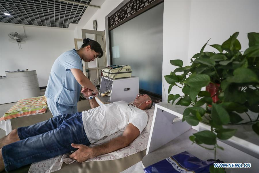 A Russian patient receives physiotherapy at Tanggangzi Hospital in Anshan, northeast China\'s Liaoning Province, June 4, 2019. Featured with traditional Chinese medicine therapy, Tanggangzi Hospital has attracted many Russian patients who come here to receive rehabilitation treatments, such as acupuncture, physiotherapy, cephalic magnet therapy. The hospital received more than 6,000 Russian patients in one year at the peak. (Xinhua/Pan Yulong)
