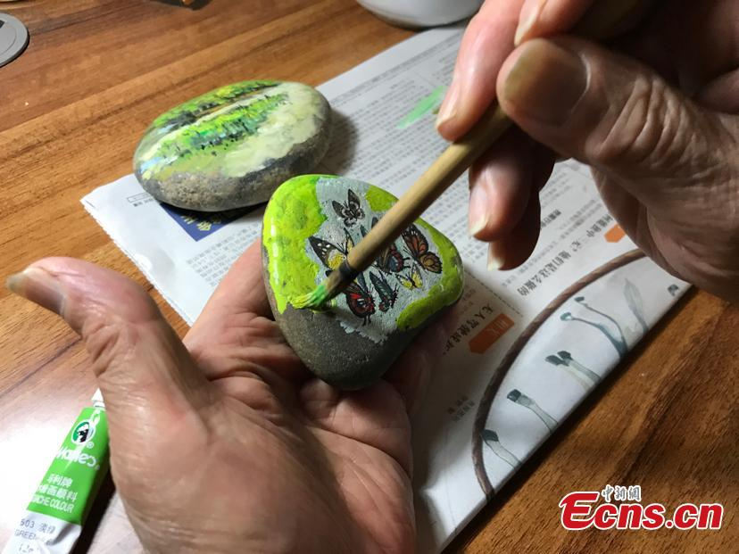 Zhang Yulin gives a final touch on his painting on a stone. Zhang Yulin, 81, from southwest China's Chongqing municipality, collects stones from the Yangtze River banks and turns them into artworks with paintings.  (Photo: China News Service/ Xiao Jiangchuan)