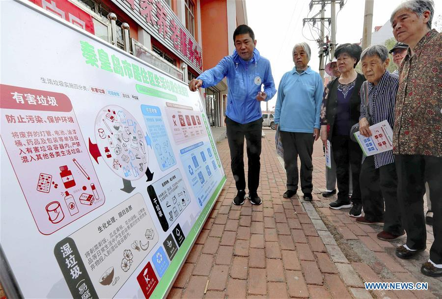 A volunteer illustrates the knowledge of garbage sorting to the local residents in Qinhuangdao, north China\'s Hebei Province, June 4, 2019. Various activities are held across the country to raise people\'s awareness of garbage sorting and help them develop the habit of waste classification. (Xinhua/Cao Jianxiong)