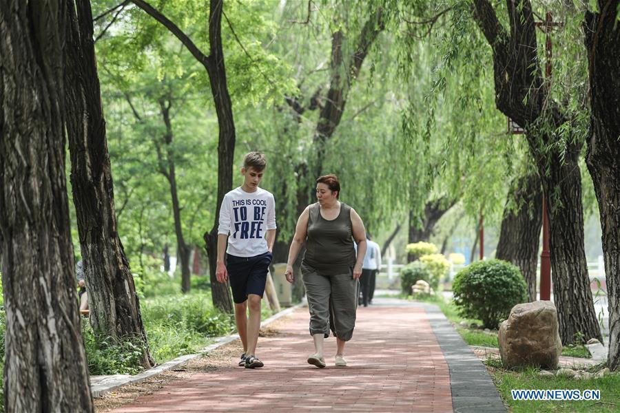 A Russian patient (R) walks with her son at Tanggangzi Hospital in Anshan, northeast China\'s Liaoning Province, June 4, 2019. Featured with traditional Chinese medicine therapy, Tanggangzi Hospital has attracted many Russian patients who come here to receive rehabilitation treatments, such as acupuncture, physiotherapy, cephalic magnet therapy. The hospital received more than 6,000 Russian patients in one year at the peak. (Xinhua/Pan Yulong)
