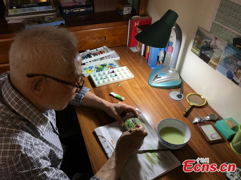 Zhang Yulin gives a final touch on his painting on a stone. Zhang, 81, from southwest China's Chongqing municipality, collects stones from the Yangtze River banks and turns them into artworks with paintings.  (Photo: China News Service/Xiao Jiangchuan)