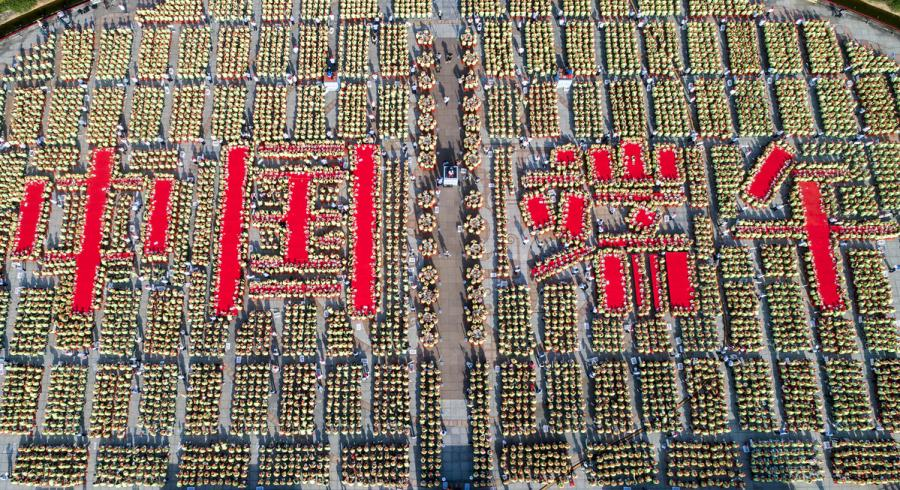 A bird\'s-eye view of the 9,478 people making zongzi, forming four Chinese characters that read \