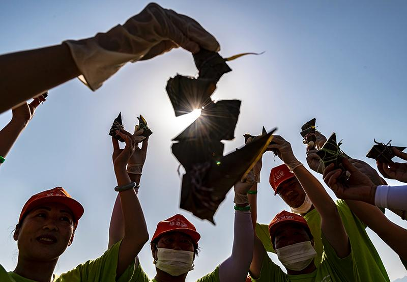 After setting a new mark recognized by Guinness World Records, people hold up their zongzi in Central China\'s Hubei Province, June 3, 2019.  (Photo Provided to chinadaily.com.cn)