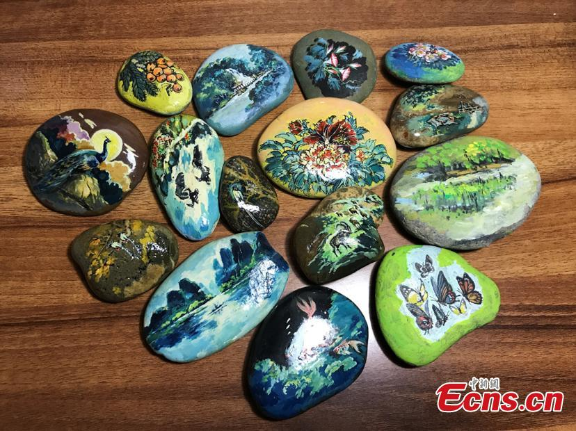 Zhang Yulin shows his paintings on stones.Zhang, 81, from southwest China's Chongqing municipality, collects stones from the Yangtze River banks and turns them into artworks with paintings.  (Photo: China News Service/Xiao Jiangchuan)