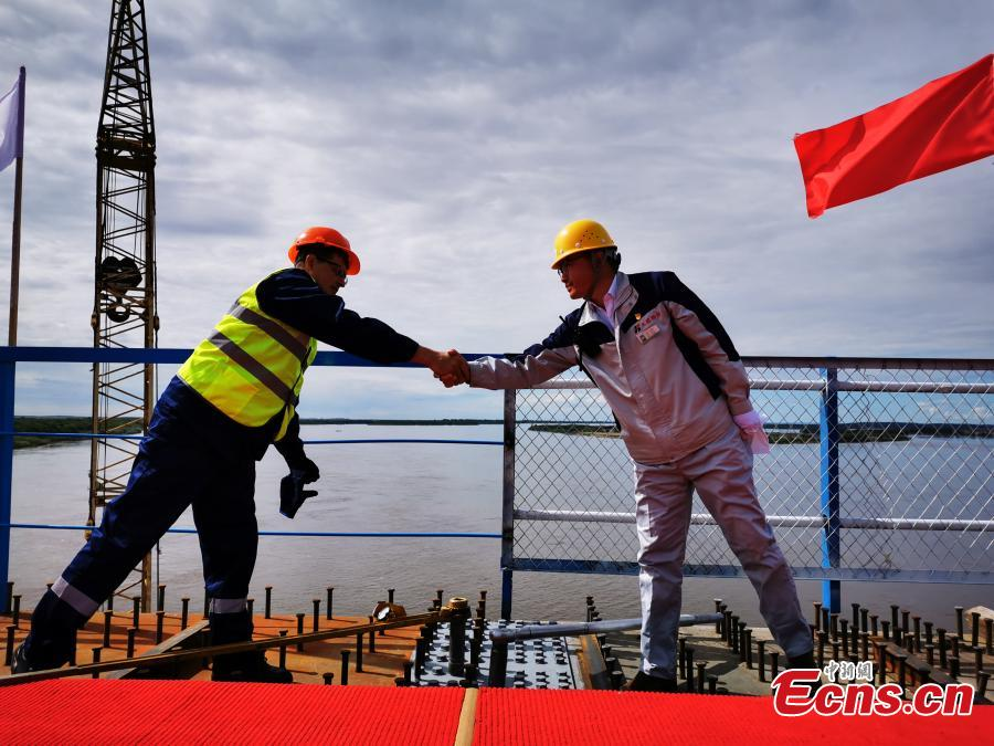 Construction workers from China and Russia shake hands after putting in the last bolts to connect the highway bridge across the Heilongjiang River, called the Amur River in Russia.  (Photo: China News Service/Shao Guoliang)