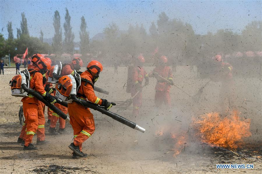 Newly-recruited firemen put out fire during a training in Hohhot, north China\'s Inner Mongolia Autonomous Region, June 5, 2019. Over 1,100 socially-recruited firemen are receiving a six-month training in Hohhot. (Xinhua/Peng Yuan)