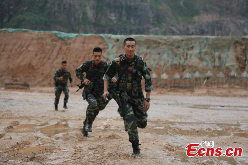 Armed police from the Snow Leopard Commando Unit undergoing intensive training in a hilly area under the blazing sun interrupted by a rainstorm. The training to last a week includes programs challenging the body and mind such as rescue missions and disposal of explosive ordnance. The Snow Leopard Commando Unit created in 2002 is mainly tasked with urban anti-terrorism missions and has safeguarded dozens of major events such as the Beijing Olympic Games, Xinhua reported. (Photo: China News Service/Li Jun)