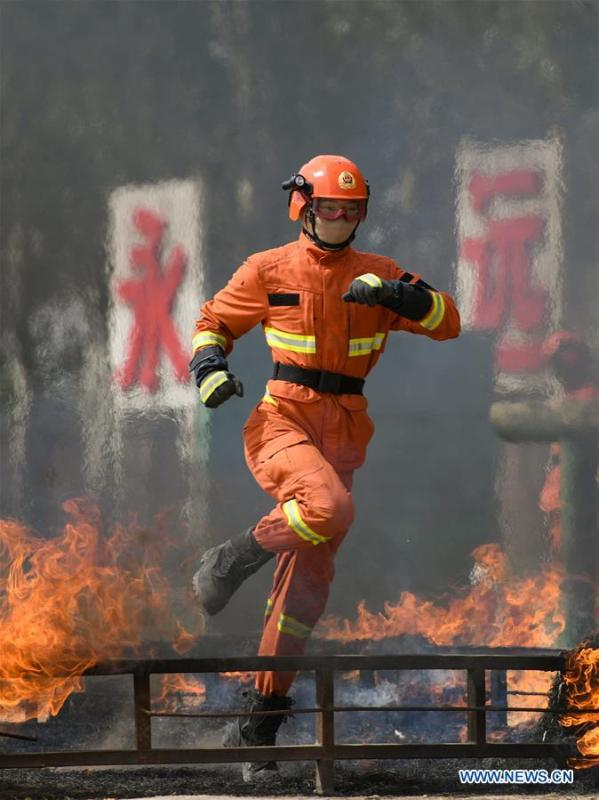 A newly-recruited fireman leaps over a fire barrier during a training in Hohhot, north China\'s Inner Mongolia Autonomous Region, June 5, 2019. Over 1,100 socially-recruited firemen are receiving a six-month training in Hohhot. (Xinhua/Peng Yuan)