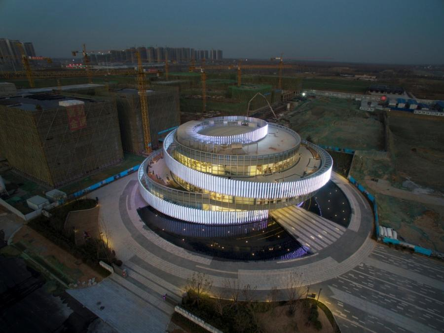 An evening aerial view shows the Exhibition Center of the Zhengzhou Linkong Biopharmaceutical Park, in Zhengzhou in Central China\'s Henan province. The building\'s design won a silver award of A\' Design Award 2019 for its architectural form, which was inspired by double-helix DNA. (Photo provided to chinadaily.com.cn)