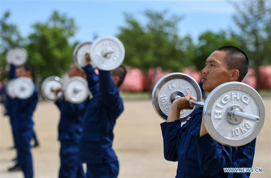 Newly-recruited firemen do physical exercises with barbells during a training in Hohhot, north China\'s Inner Mongolia Autonomous Region, June 5, 2019. Over 1,100 socially-recruited firemen are receiving a six-month training in Hohhot. (Xinhua/Peng Yuan)