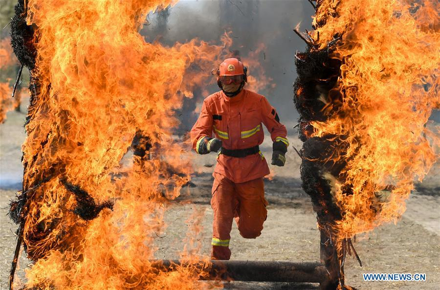 A newly-recruited fireman runs through a fire wall during a training in Hohhot, north China\'s Inner Mongolia Autonomous Region, June 5, 2019. Over 1,100 socially-recruited firemen are receiving a six-month training in Hohhot. (Xinhua/Peng Yuan)