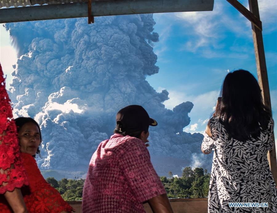People watch the Mount Sinabung spewing thick ash in Karo, North Sumatra, Indonesia, June 9, 2019. A column of thick ash was spewed seven km high to the sky from the crater of Mount Sinabung volcano in Sumatra Island of western Indonesia on Sunday, the country\'s national volcanology agency said. (Xinhua/Anto Sembiring)
