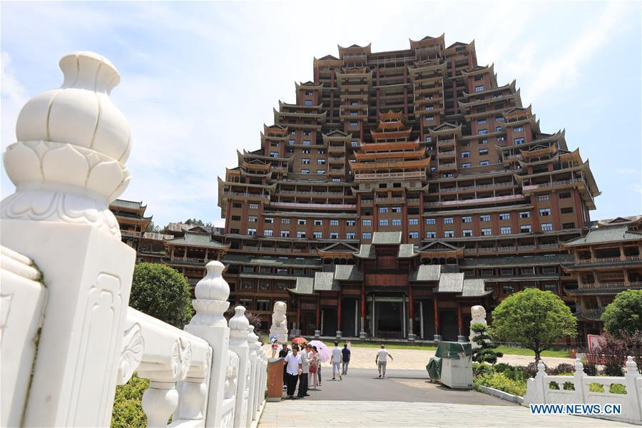 Tourists visit a wooden building of Shui ethnic group in Yingshan Town of Dushan County, southwest China\'s Guizhou Province, June 7, 2019. The 24-story, 99.9-meter-high traditional Shui-style wooden building in Dushan is of \