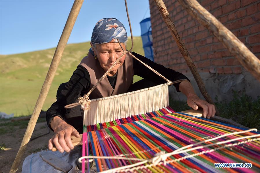 A herdswoman is seen weaving in a pasturing area at Fuhai County of Altay, northwest China\'s Xinjiang Uygur Autonomous Region, on June 5, 2019. As summer comes, herdsmen of Kazak ethnic group here are busy with transferring livestock to summer pastures. (Xinhua/Ding Lei)