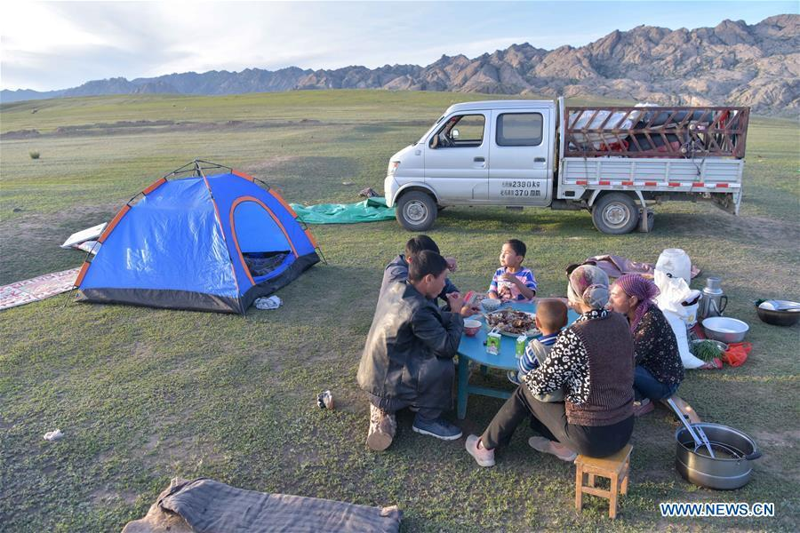 People have dinner during their transfer to summer pasture in Fuhai County of Altay, northwest China\'s Xinjiang Uygur Autonomous Region, on June 5, 2019. As summer comes, herdsmen of Kazak ethnic group here are busy with transferring livestock to summer pastures. (Xinhua/Ding Lei)