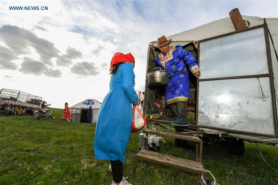 A family unload daily necessities from a truck during the nomadic migration on the Ar Horqin grassland in Chifeng City, north China\'s Inner Mongolia Autonomous Region, June 1, 2019. Yearly nomadic grazing is still a tradition for people live on the Ar Horqin grassland, where was listed of National Important Agricultural Heritage Systems in 2014. For a long time, herdsmen would decide the route and time of yearly nomadic grazing according to the growth of grassland. (Xinhua/Peng Yuan)