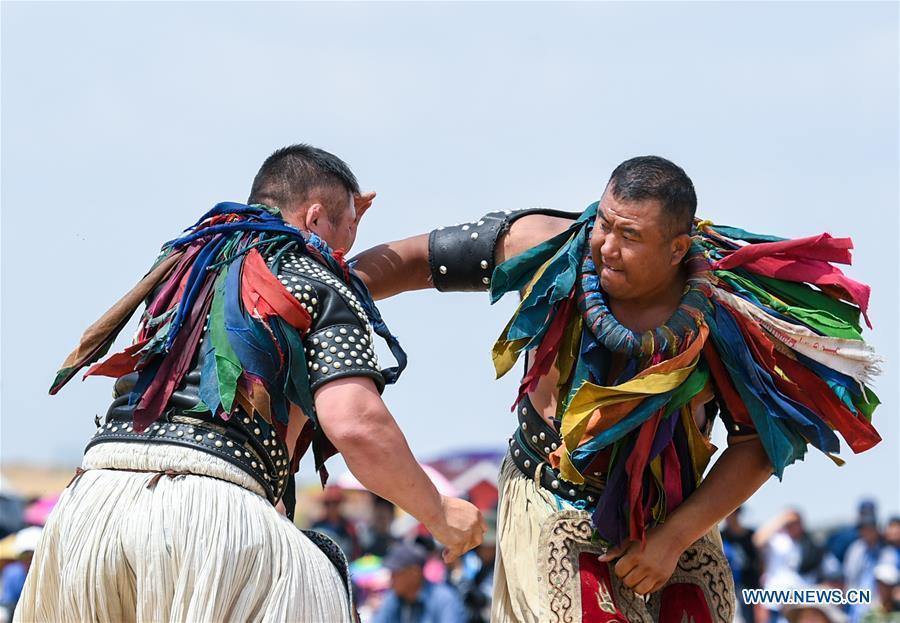 Participants take part in a wrestling contest during a desert Nadam Fair held in Naiman Banner, Tongliao City, north China\'s Inner Mongolia Autonomous Region, June 10, 2019. (Xinhua/Peng Yuan)