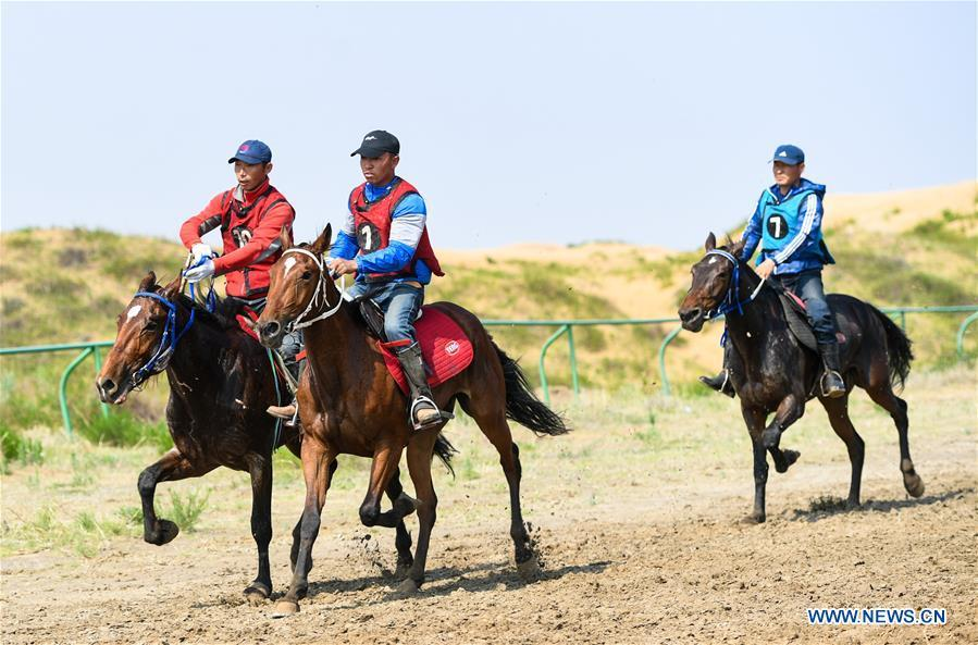 Participants take part in a horse riding contest during a desert Nadam Fair held in Naiman Banner, Tongliao City, north China\'s Inner Mongolia Autonomous Region, June 10, 2019. (Xinhua/Peng Yuan)