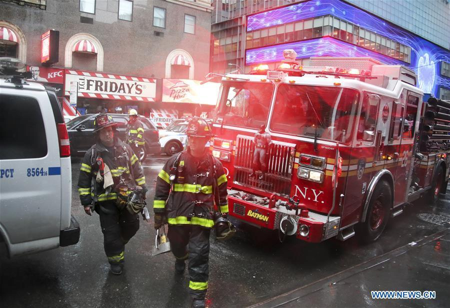 Fire fighters walk on the street near the building where a helicopter crashed in Manhattan, New York, the United States, June 10, 2019. One person was killed after a helicopter crashed onto the roof of a skyscraper in Midtown Manhattan of New York City Monday afternoon, according to media reports. (Xinhua/Wang Ying)