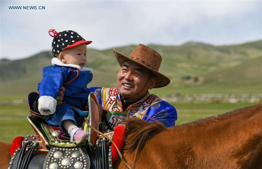 A herdsman puts his son on the horseback during the nomadic migration on the Ar Horqin grassland in Chifeng City, north China\'s Inner Mongolia Autonomous Region, May 31, 2019. Yearly nomadic grazing is still a tradition for people live on the Ar Horqin grassland, where was listed of National Important Agricultural Heritage Systems in 2014. For a long time, herdsmen would decide the route and time of yearly nomadic grazing according to the growth of grassland. (Xinhua/Peng Yuan)
