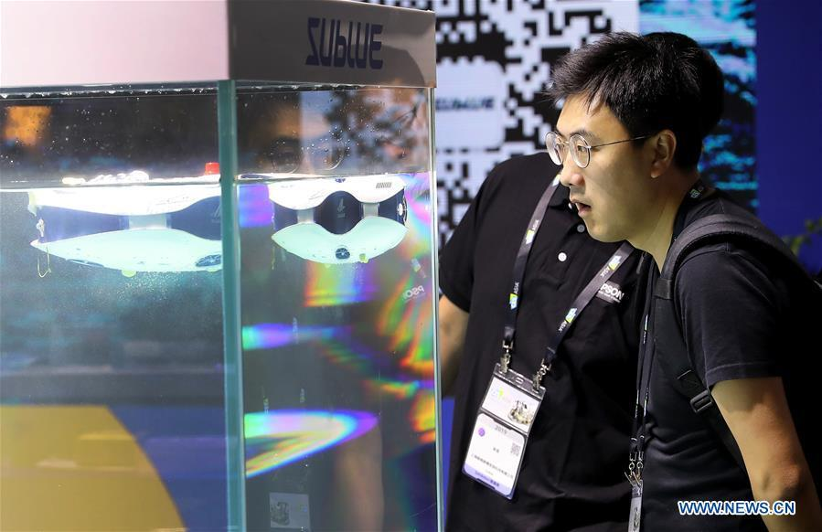 Visitors view underwater photographic robots during the 2019 Consumer Electronics Show (CES) Asia in east China\'s Shanghai, June 11, 2019. The 2019 Consumer Electronics Show (CES) Asia kicked off on Tuesday in Shanghai. The three-day exhibition showcased the latest achievements in 5G technology, artificial intelligence, augmented/virtual reality and vehicle technology. (Xinhua/Fang Zhe)