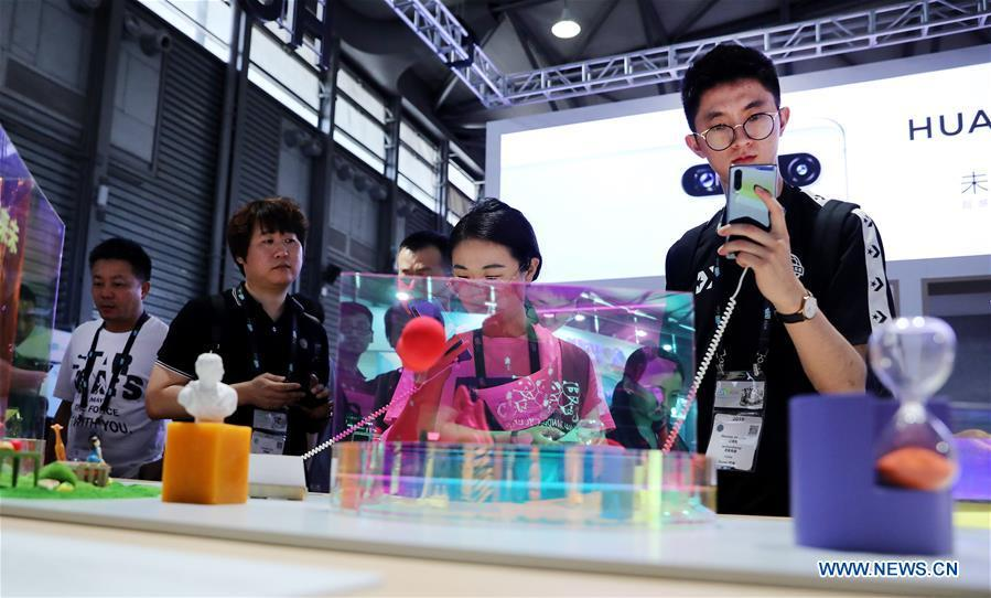 Visitors try mobile phones during the 2019 Consumer Electronics Show (CES) Asia in east China\'s Shanghai, June 11, 2019. The 2019 Consumer Electronics Show (CES) Asia kicked off on Tuesday in Shanghai. The three-day exhibition showcased the latest achievements in 5G technology, artificial intelligence, augmented/virtual reality and vehicle technology. (Xinhua/Fang Zhe)