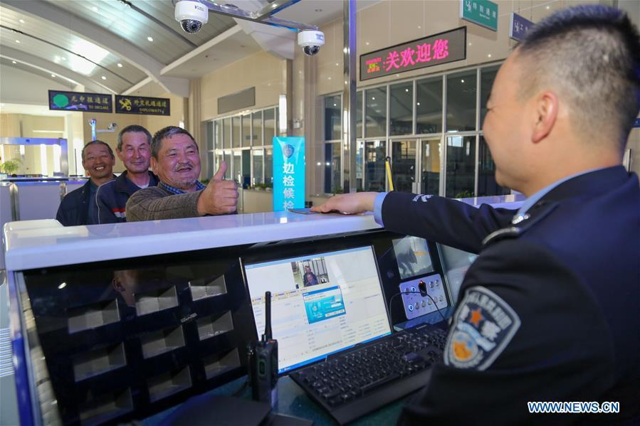 Tourists from Kyrgyzstan give thumbs-up to a policeman at a border inspection station of Irkeshtam port in northwest China\'s Xinjiang Uygur Autonomous Region on June 11, 2019. Irkeshtam is China\'s far west land port open to Kyrgyzstan. (Xinhua/Luo Yang)