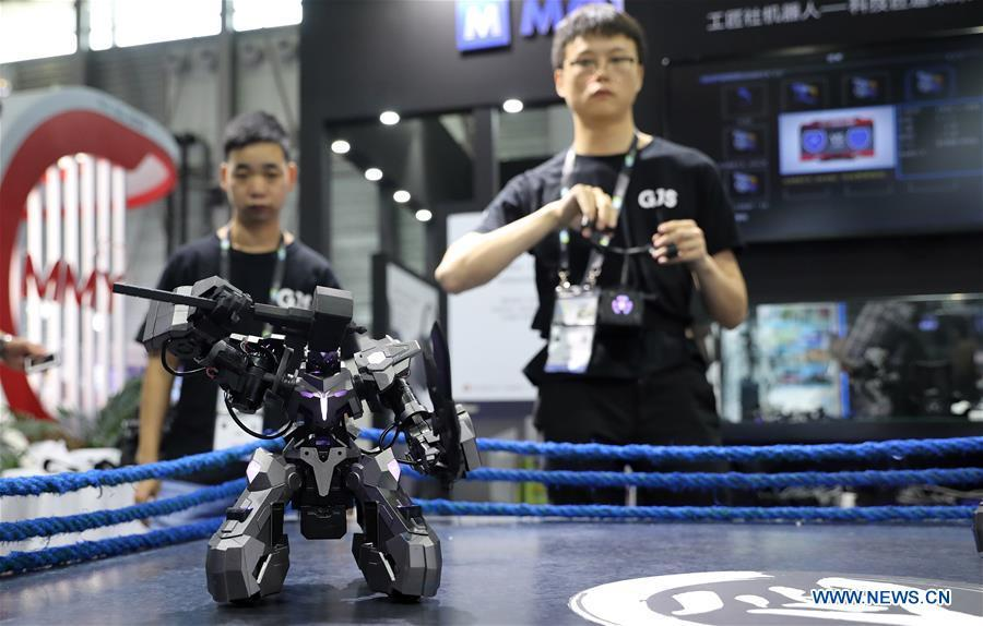 A staff member (R) demonstrates a fighting robot during the 2019 Consumer Electronics Show (CES) Asia in east China\'s Shanghai, June 11, 2019. The 2019 Consumer Electronics Show (CES) Asia kicked off on Tuesday in Shanghai. The three-day exhibition showcased the latest achievements in 5G technology, artificial intelligence, augmented/virtual reality and vehicle technology. (Xinhua/Fang Zhe)