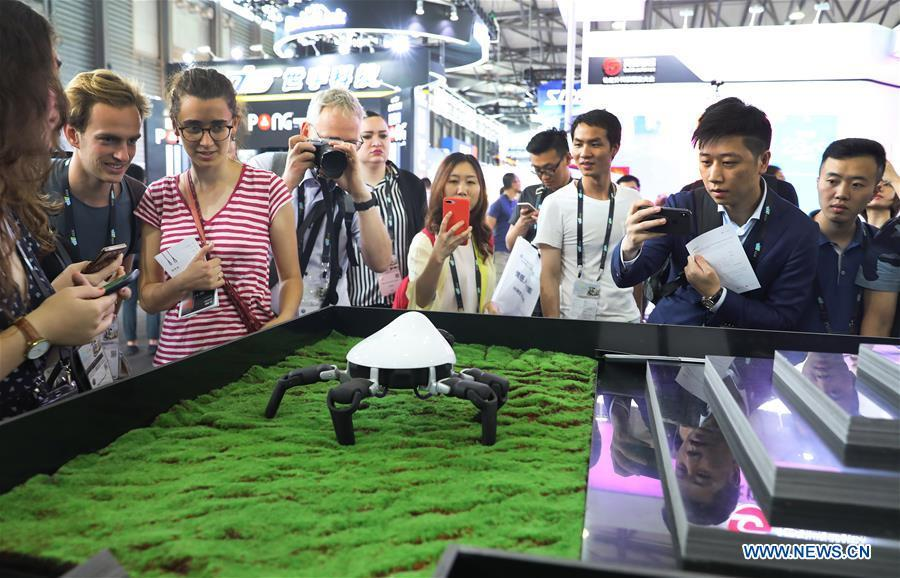 Visitors view a spider-like programmable robot with six legs during the 2019 Consumer Electronics Show (CES) Asia in east China\'s Shanghai, June 11, 2019. The 2019 Consumer Electronics Show (CES) Asia kicked off on Tuesday in Shanghai. The three-day exhibition showcased the latest achievements in 5G technology, artificial intelligence, augmented/virtual reality and vehicle technology. (Xinhua/Fang Zhe)