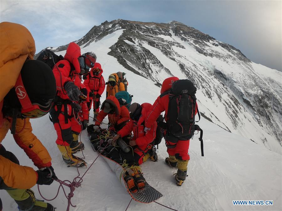 Chinese rescuers prepare to carry an Australian climber downhill at the north slope of the Mount Qomolangma, May 22, 2019. (Xinhua)