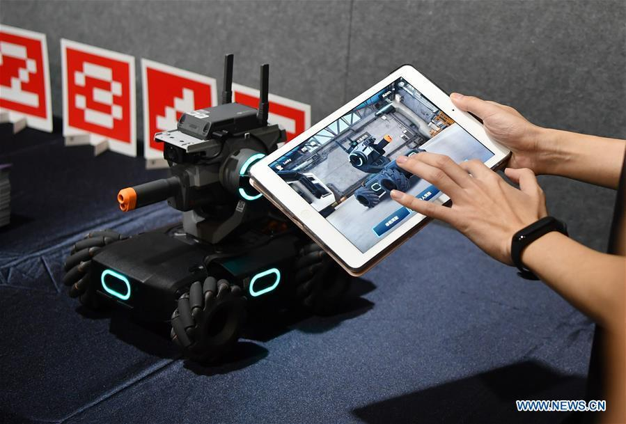 A staff member demonstrates an educational robot produced by Chinese drone maker DJI at an event in Beijing, capital of China, June 12, 2019. DJI launched its first educational robot RoboMaster S1 at an event on Wednesday. The robot, supporting 2 programming languages, features a configuration of 31 sensors and 46 programmable components. (Xinhua/Wang Qingqin)