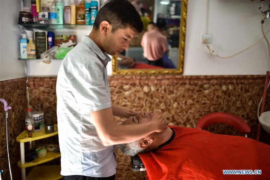 A barber provides shaving service for a local resident in the ancient city of Kashgar, northwest China\'s Xinjiang Uygur Autonomous Region, June 12, 2019. The ancient city of Kashgar has been well prepared for the peak tourism season through multiple measures including improving infrastructure and service quality as well as staging acrobatics performances to help tourists better experience the time-honored folk culture here. (Xinhua/Zhao Ge)