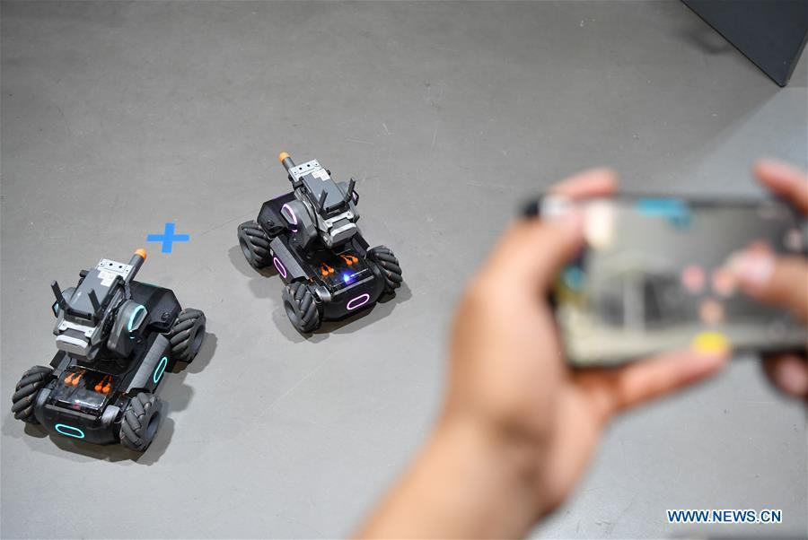 A staff member demonstrates educational robots produced by Chinese drone maker DJI at an event in Beijing, capital of China, June 12, 2019. DJI launched its first educational robot RoboMaster S1 at an event on Wednesday. The robot, supporting 2 programming languages, features a configuration of 31 sensors and 46 programmable components. (Xinhua/Wang Qingqin)