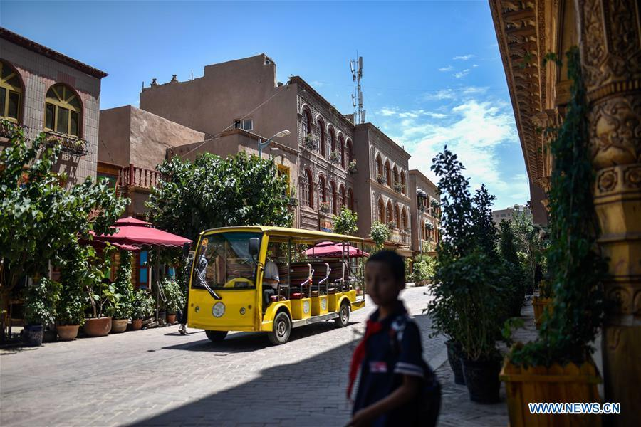 An electric-powered vehicle runs on a road in the ancient city of Kashgar, northwest China\'s Xinjiang Uygur Autonomous Region, June 12, 2019. The ancient city of Kashgar has been well prepared for the peak tourism season through multiple measures including improving infrastructure and service quality as well as staging acrobatics performances to help tourists better experience the time-honored folk culture here. (Xinhua/Zhao Ge)